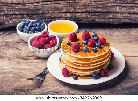 Pancakes with blueberries , honey & raspberry on wood background . - stock photo