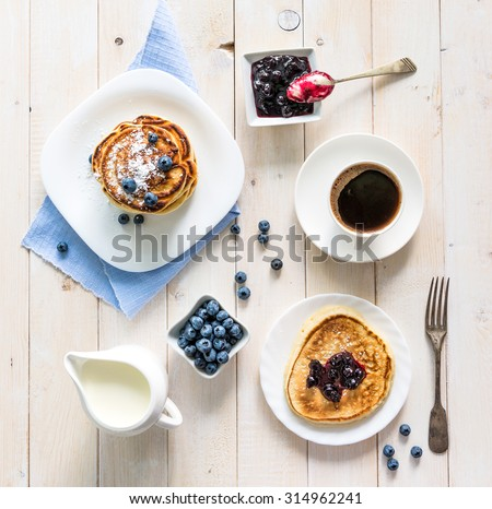 pancakes with blueberry and coffee on wooden background. top view - stock photo