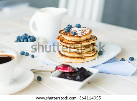 pancakes with blueberry and jam on white wooden table - stock photo