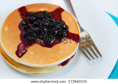 Pancakes with blueberry jam on a plate - stock photo