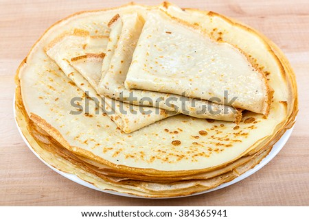 Pancakes with butter on the plate on a wooden background.