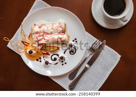 Pancakes with cherry jam beautifully decorated with flowers of fruit and chocolate on a white plate, which stands on a wooden table near the window in the interior cozy cafe. Shallow depth of field. - stock photo