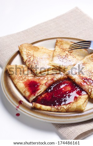 Pancakes with cherry jam on table