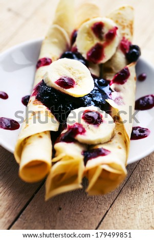 Pancakes with cottage cheese in the middle and berry sauce,bananas closeup on a plate for pancake day/ Sweet dessert of pancakes rolls - stock photo