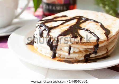 pancakes with cottage cheese, poured maple syrup and chocolate sauce