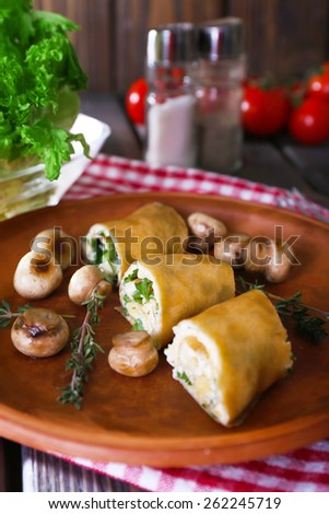 Pancakes with creamy mushrooms in plate on wooden table, closeup - stock photo