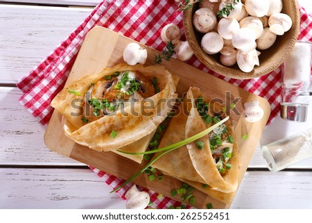 Pancakes with creamy mushrooms on cutting board on wooden table, top view - stock photo