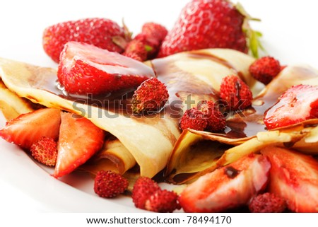 Pancakes with different strawberries with chocolate syrup on white - stock photo