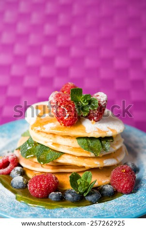 pancakes with fresh berries, honey and mint