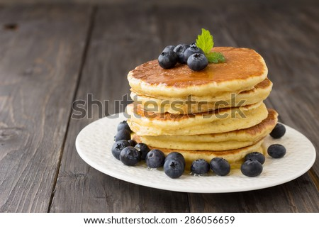 Pancakes with fresh blueberries and honey on wooden table - stock photo