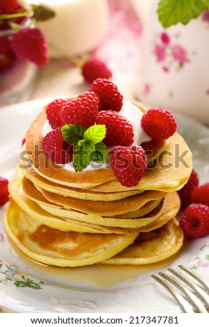 Pancakes with fresh raspberries and creamy soft cheese - stock photo