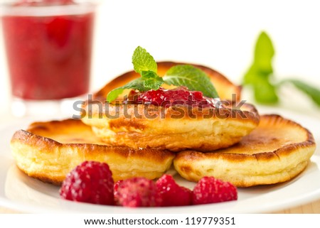pancakes with fresh raspberries and mint on a plate