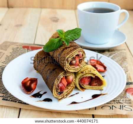 Pancakes with fresh strawberries, chocolate, decorating mint leaves and a cup of tea on a light wooden background. Breakfast. - stock photo