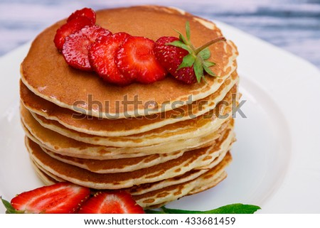 Pancakes with fresh strawberry and mint on white plate on blue wooden background. Closeup.