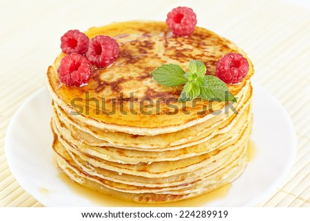 Pancakes with honey, raspberry and a mint branch - stock photo