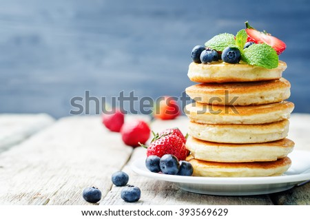 pancakes with honey, strawberries and blueberries on white wood background. toning. selective focus - stock photo