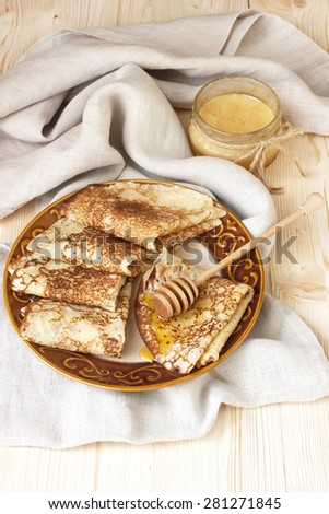 Pancakes with honey syrup on ceramic plate. - stock photo