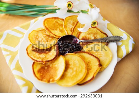 Pancakes with jam and spoon on a plate and white daffodils on wooden background. Top view - stock photo