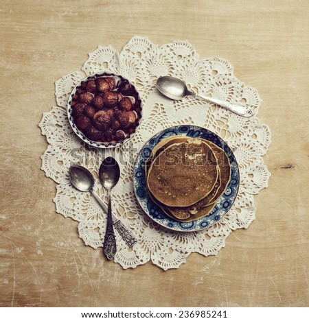 Pancakes with jam and spoon on the old patterned napkins on wooden table - stock photo