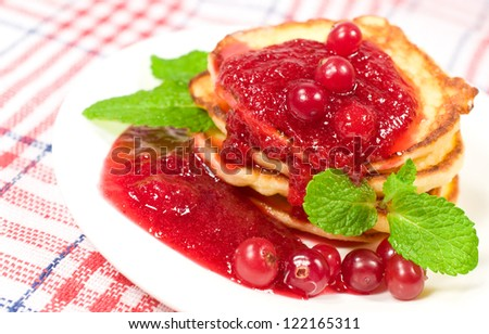 pancakes with jam , berries and mint leaves