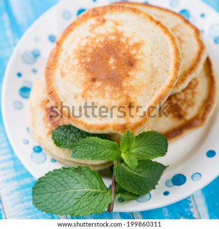 Pancakes with mint on a glass plate, studio shot, close-up - stock photo