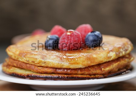 Pancakes with raspberry, blueberry and maple syrup, on oak wooden table - stock photo