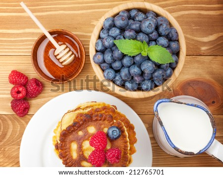 Pancakes with raspberry, blueberry, milk and honey syrup. On wooden table - stock photo