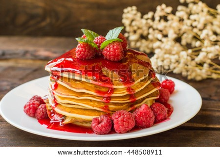 Pancakes with raspberry jam and fresh berries. Wooden background. Close-up
