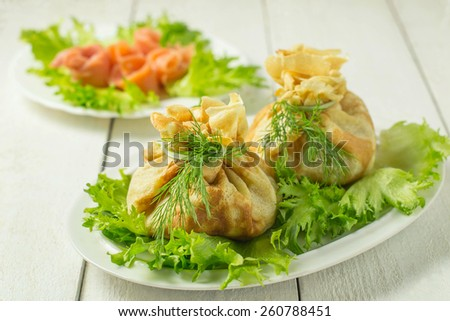 Pancakes with salmon, cream cheese and herbs. Bags, tied with dill on a plate with salad. Selective focus  - stock photo