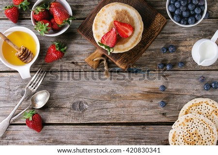 Pancakes with strawberries and blueberries, bowls of honey and jug of milk over old wooden background. Breakfast concept background. Flat lay, space for text