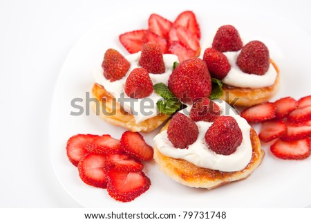 Pancakes with strawberries and cream on white plate