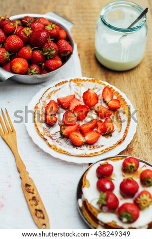 Pancakes with  strawberries and sour cream. Stack of pancakes with fresh strawberry and balsamic glase in frying pan on wooden table. Rustic style  - stock photo