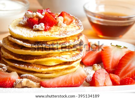 Pancakes with strawberries, nuts and maple syrup - stock photo