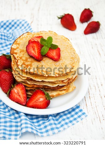 Pancakes with strawberries on a wooden background