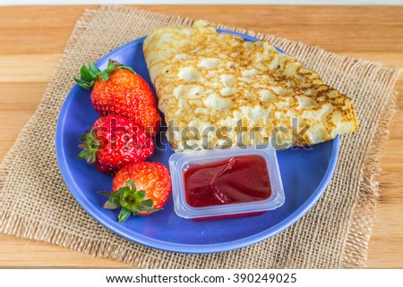 pancakes with strawberries on a wooden background. - stock photo