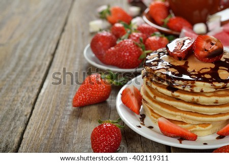 Pancakes with strawberries on a wooden background - stock photo