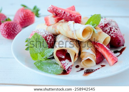 Pancakes with strawberry fruits and chocolate topping and white castor sugar - stock photo