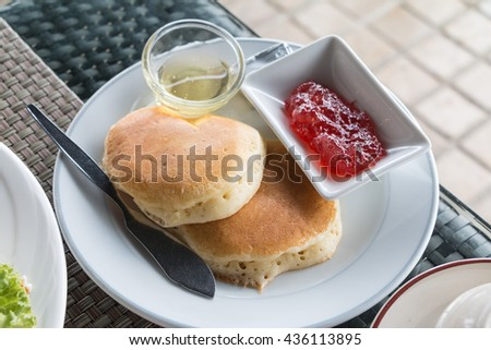 Pancakes with strawberry jam and honey close up. - stock photo