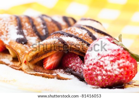 Pancakes with the strawberries on a plate, macro