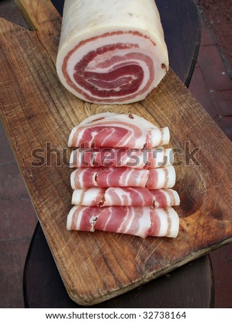 Pancetta, typical italian roll raw bacon with slices on wood trencher