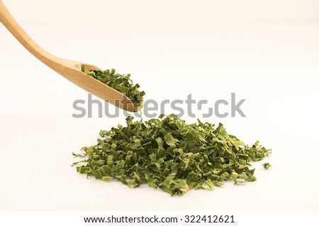 Pandan leaf tea.  Shredded pandan leaf processed and use as tea leaf for its sweet fragrance and medicinal benefits.  Straight view of bamboo spoon scoping dried leaves.  Isolated on white background. - stock photo