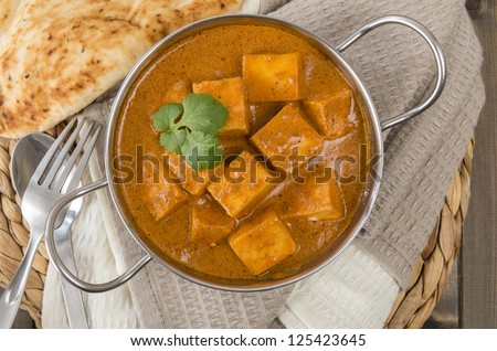 Paneer Makhani or Shahi Paneer (Paneer Butter Masala) - Indian curd cheese curry in a balti dish, served with naan bread and garnished with coriander leaves. Shot from above (overhead). - stock photo
