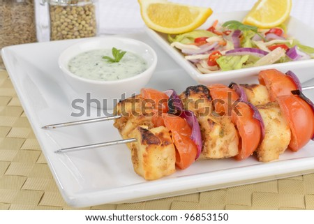 Paneer Tikka Kebab - Tadoori indian cheese skewers with tomato and red onions served with chrunchy, salad mint raita and lemon wedges. - stock photo