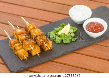 Paneer Tikka Kebab - Tandoori Indian cheese skewers served on a slate with lemon, chili sauce and cucumber and red onion yoghurt raita. - stock photo