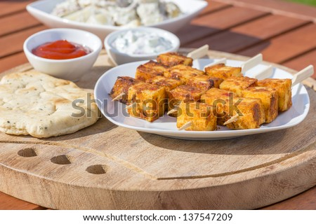Paneer Tikka Kebab - Tandoori Indian cheese skewers with naan bread, chili sauce, and cucumber and yoghurt raita. Eating outdoors! - stock photo