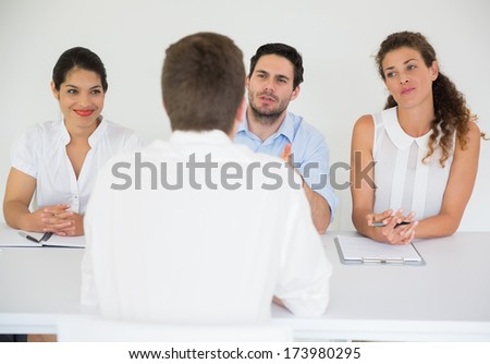Panel of business people conducting job interview with male candidate - stock photo
