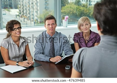Panel of business people sitting at table in meeting room conducting job interview looking at applicant. - stock photo
