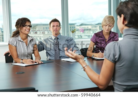 Panel of business people sitting at table in meeting room conducting job interview talking with applicant.