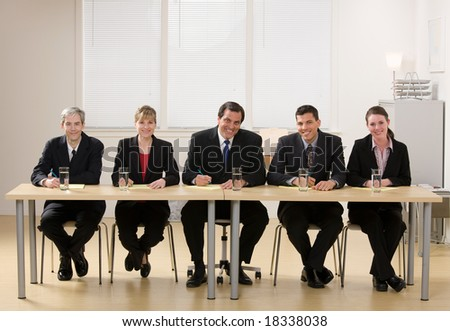Panel of co-workers about to conduct a job interview - stock photo