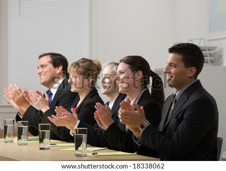 Panel of co-workers applauding - stock photo
